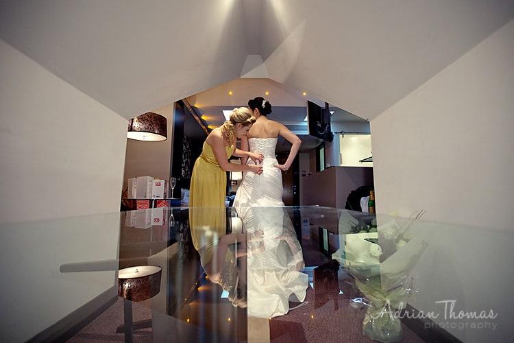 bridesmaid helping bride get dressed