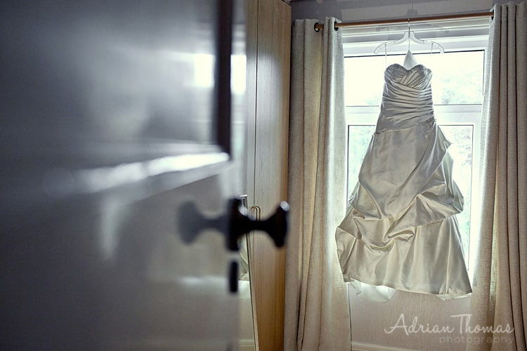 brides dress hanging on rail