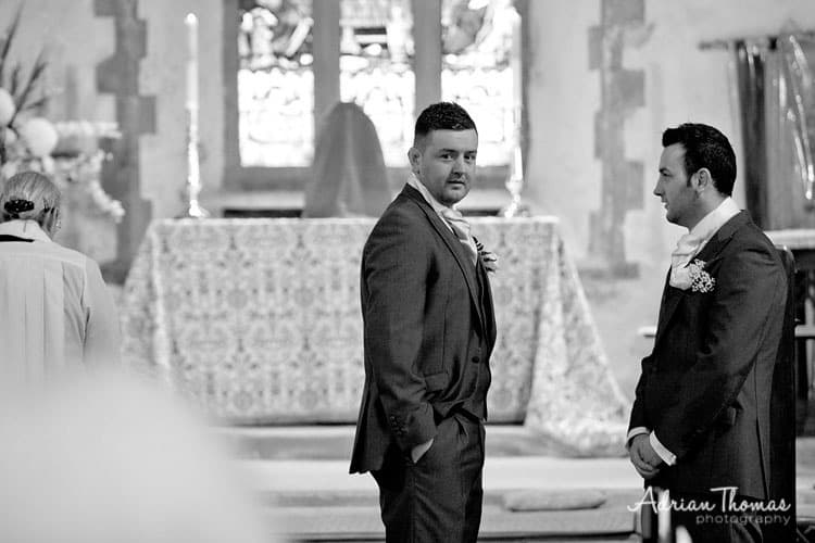 Groom watching bride walking down aisle