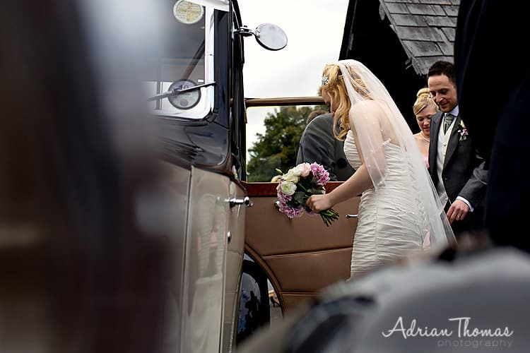 Bride getting into wedding car