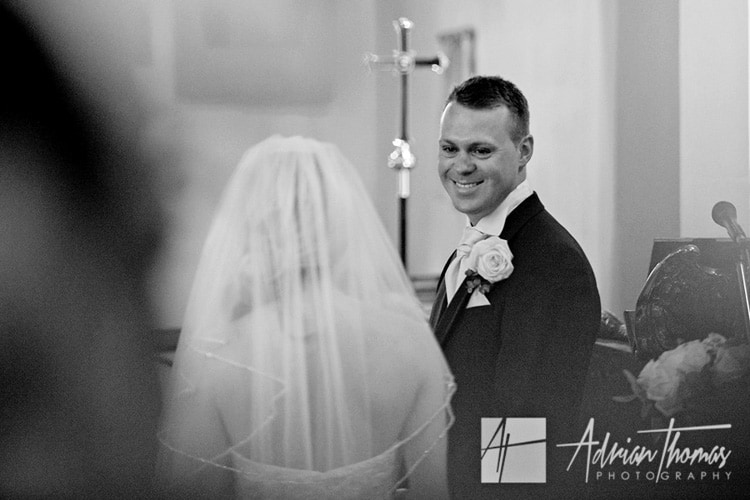 happy groom at bride walking down isle St John Baptist Church in Sully