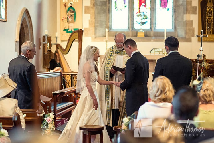 Exchange of rings during wedding at St Johns Church in Sully.