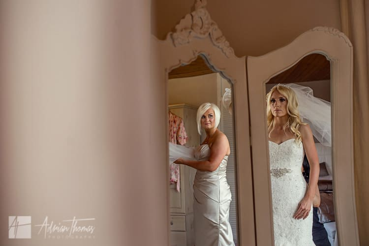 Bridesmaid looking at bride in mirror.
