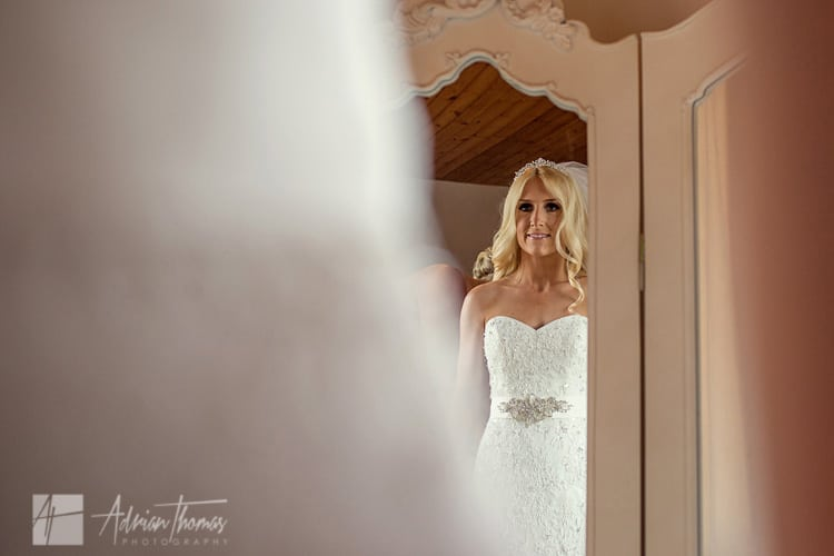Bride looking in mirror while getting dressed.