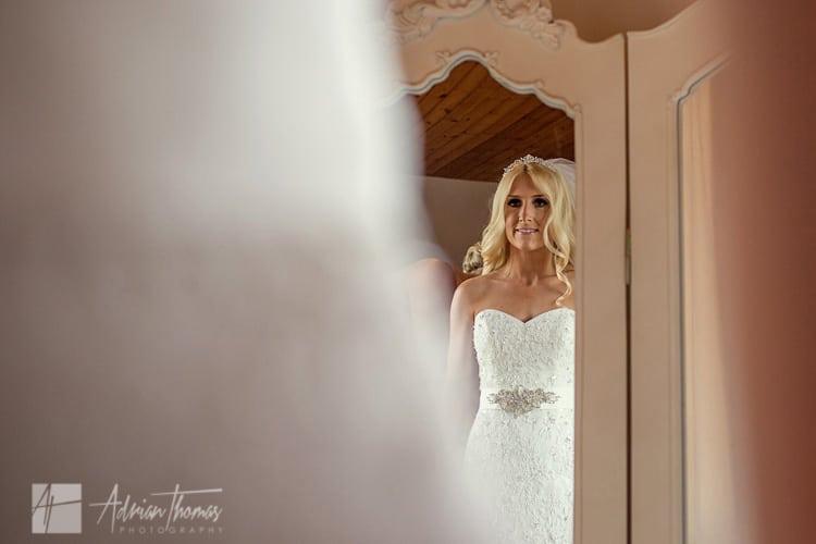 Bride looking in mirror while getting dressed.