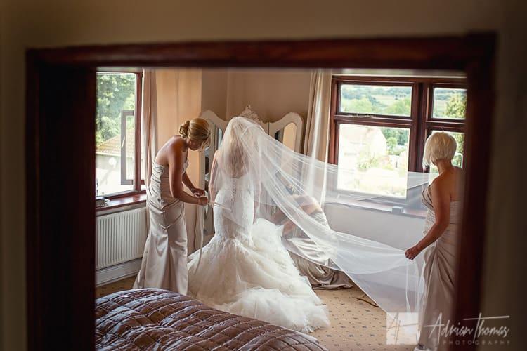 Bridesmaids help bride get dressed.