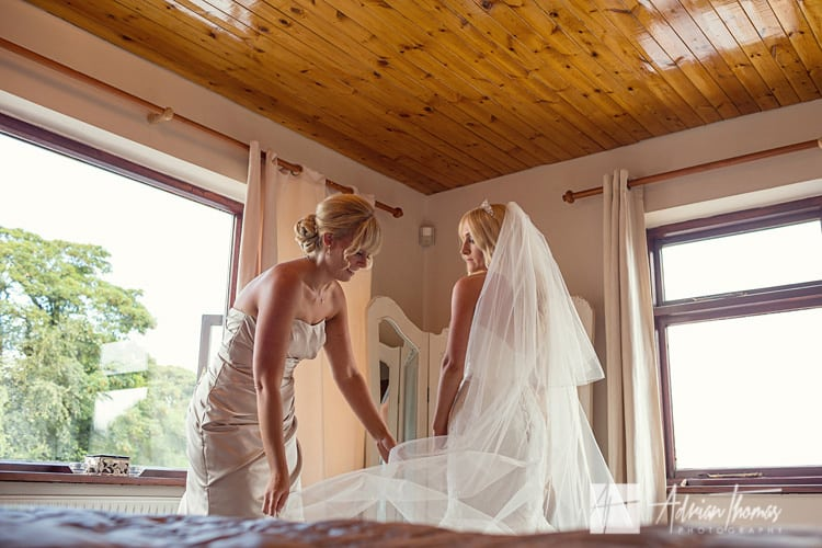Bridesmaid adjusts brides veil during preparations.