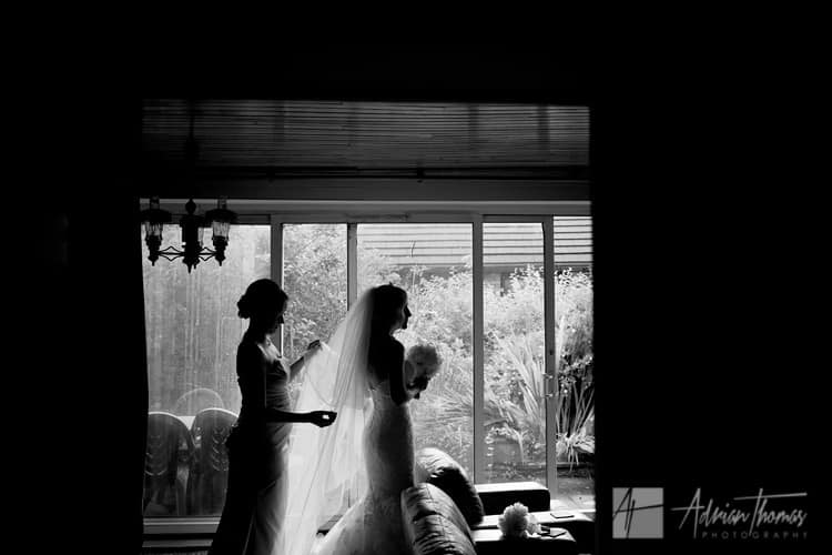 Silhouette image of bridesmaid adjusting brides veil.