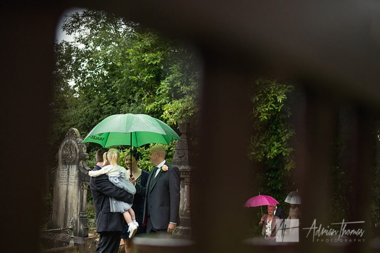 Guests arrive to wedding with umbrellas.