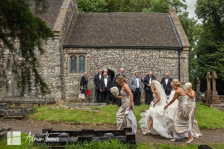 Choir onlooking as bride arrives.