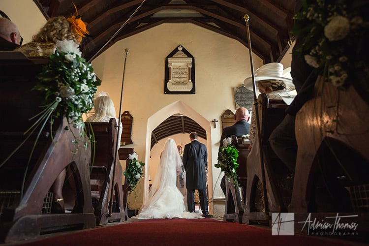 Wide angle image of bride and groom during wedding at Llanilid Church.