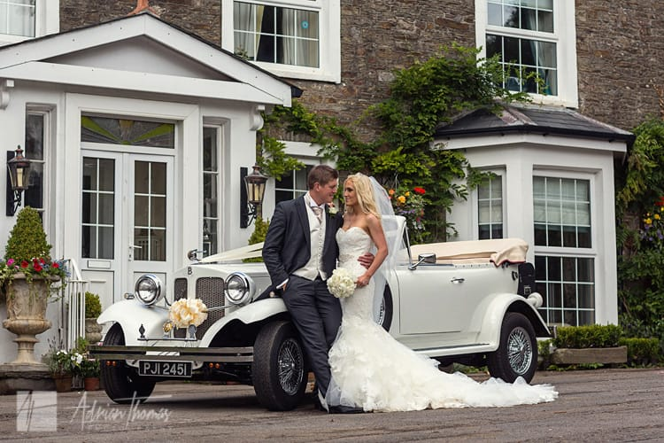 Bride and groom with wedding car outside family home.