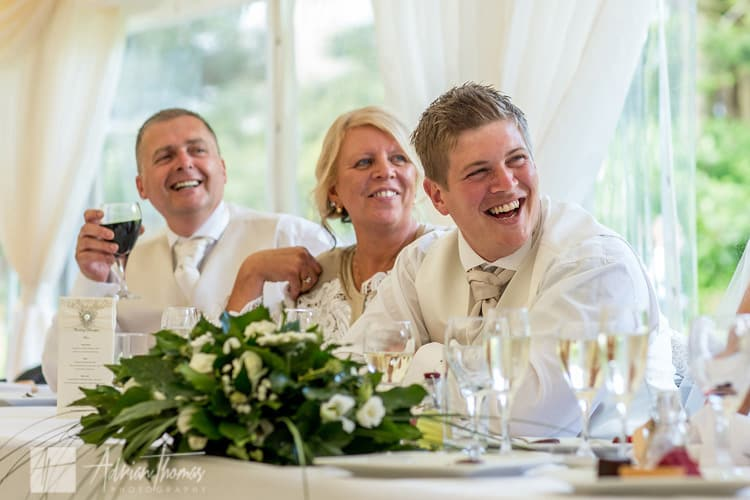 Groom laughing during speeches.