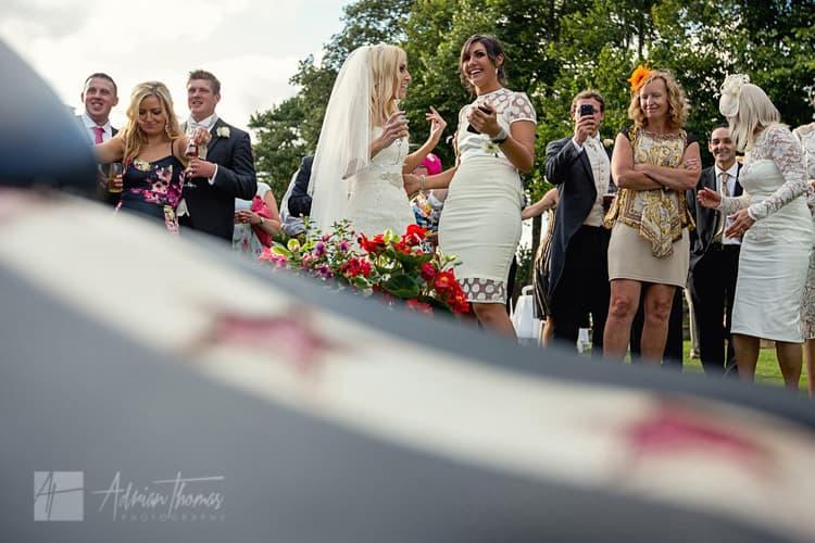 Bride and friends watch wedding signer entertainment.