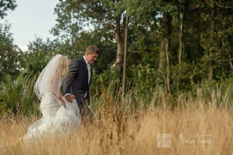 Bride and groom walking in field near Llanilid Church.