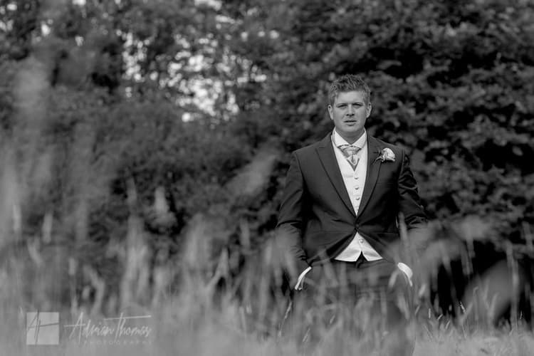 Groom in filed near marquee reception.