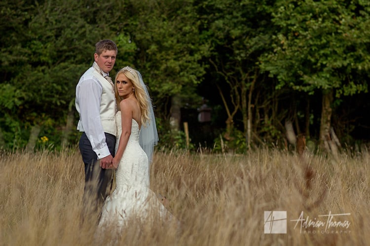 Groom and bride portrait in grass field.