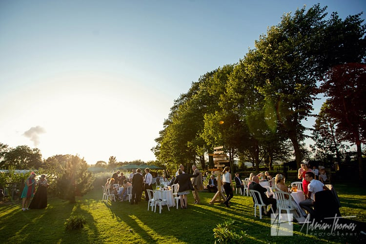 Guests enjoy sunshine and mingle at wedding reception marquee.
