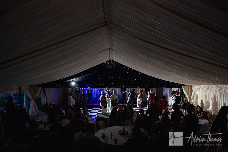 Image of wedding guests dancing in marquee at night.