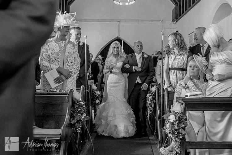 Bride waling down isle at St Llanilid Church.