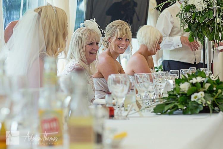 Bridesmaid laughing during wedding speech.