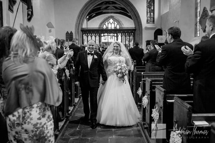 Bride and groom waling down isle at St Augustines church in Rumney.