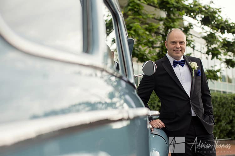 Groom at St David's Hotel Cardiff Bay wedding with his car.