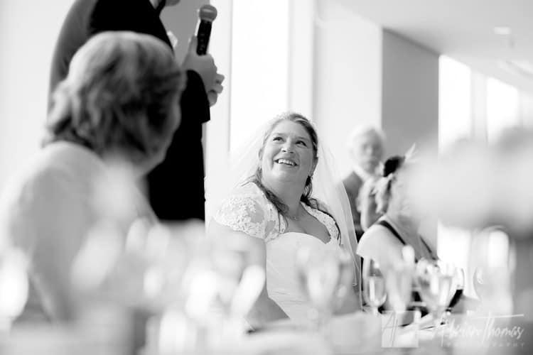 Happy bride during grooms speech.