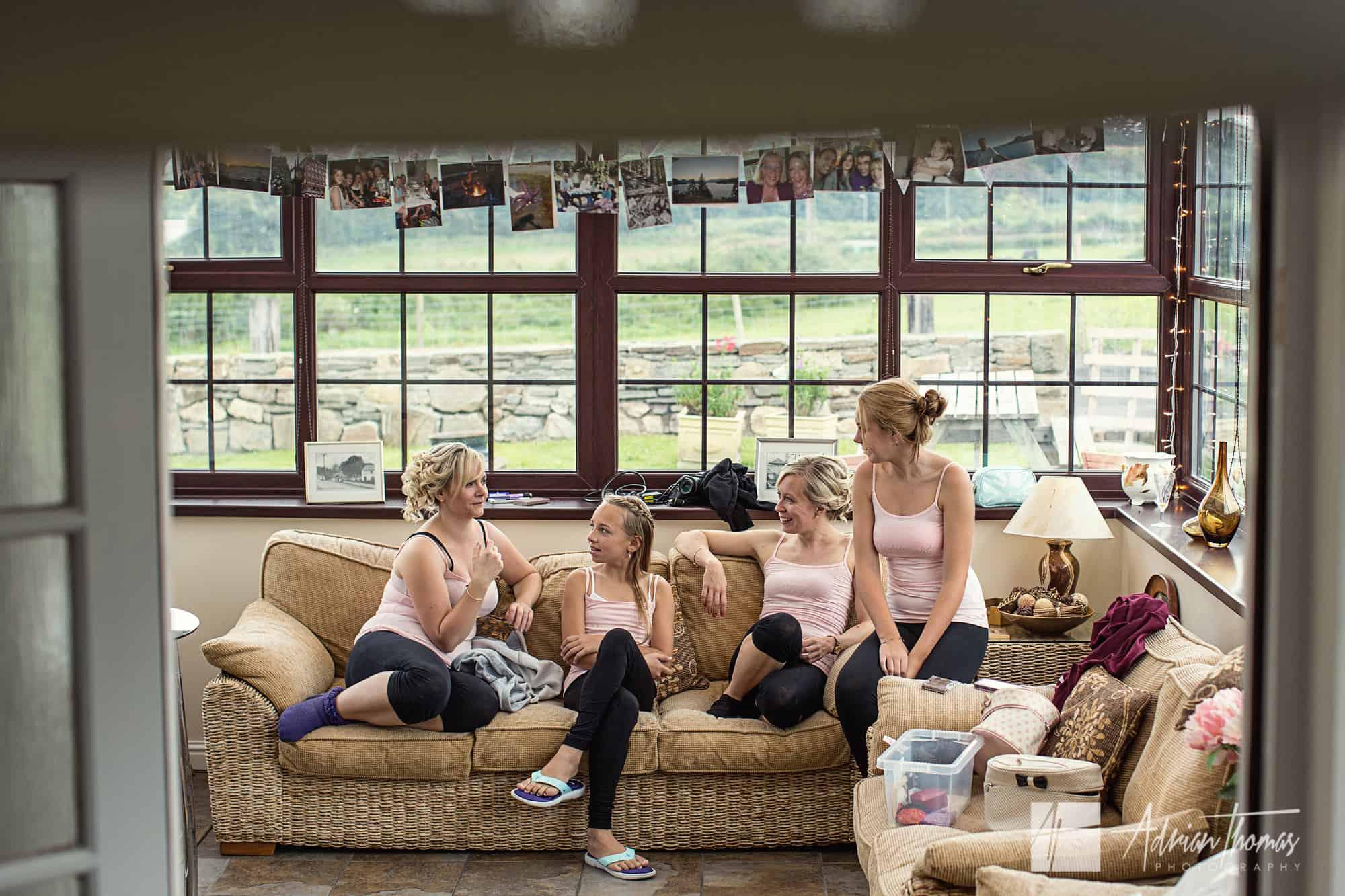 Bridesmaids chatting on settee.