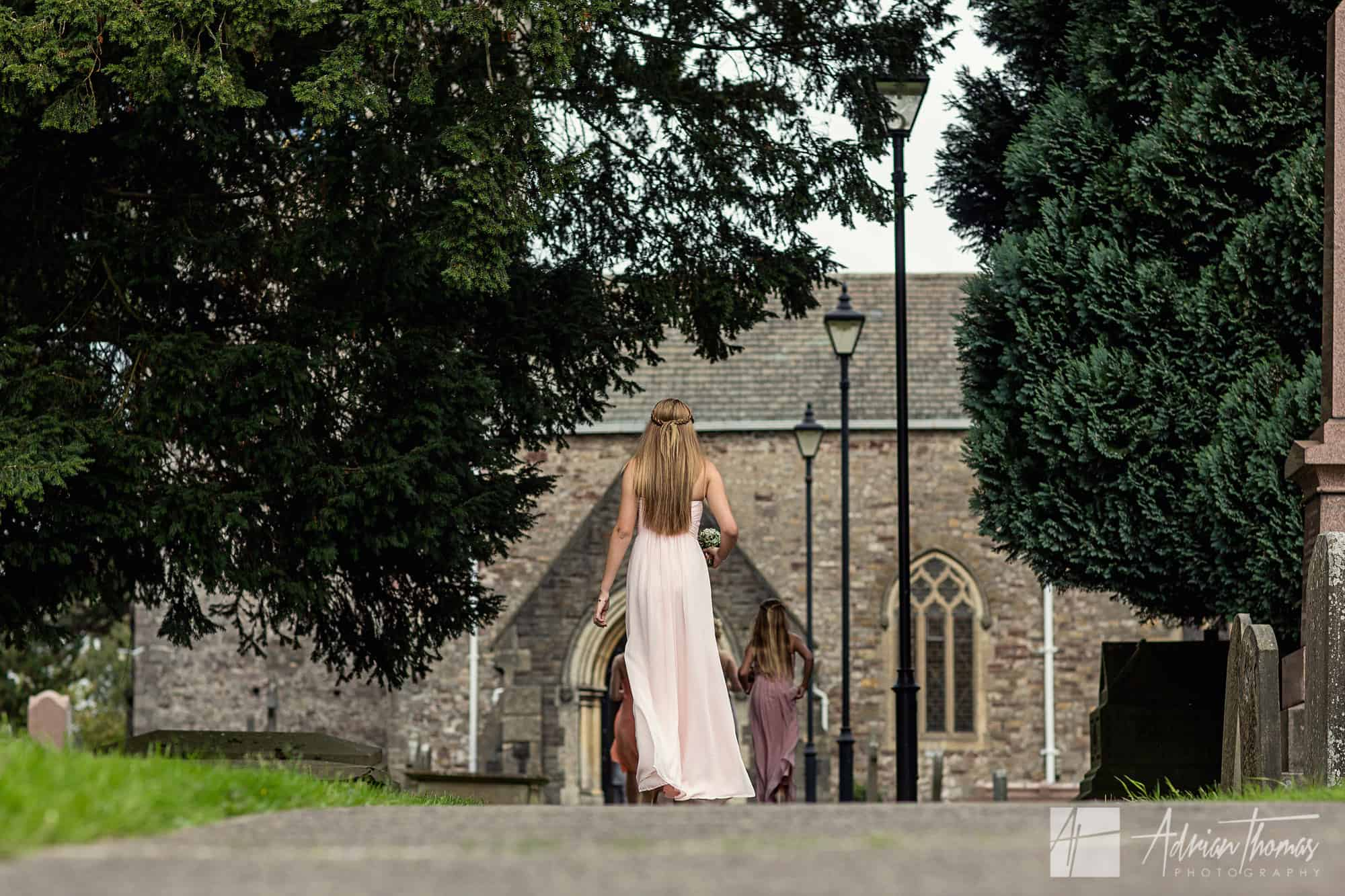 Bridesmaid walking down path at church.