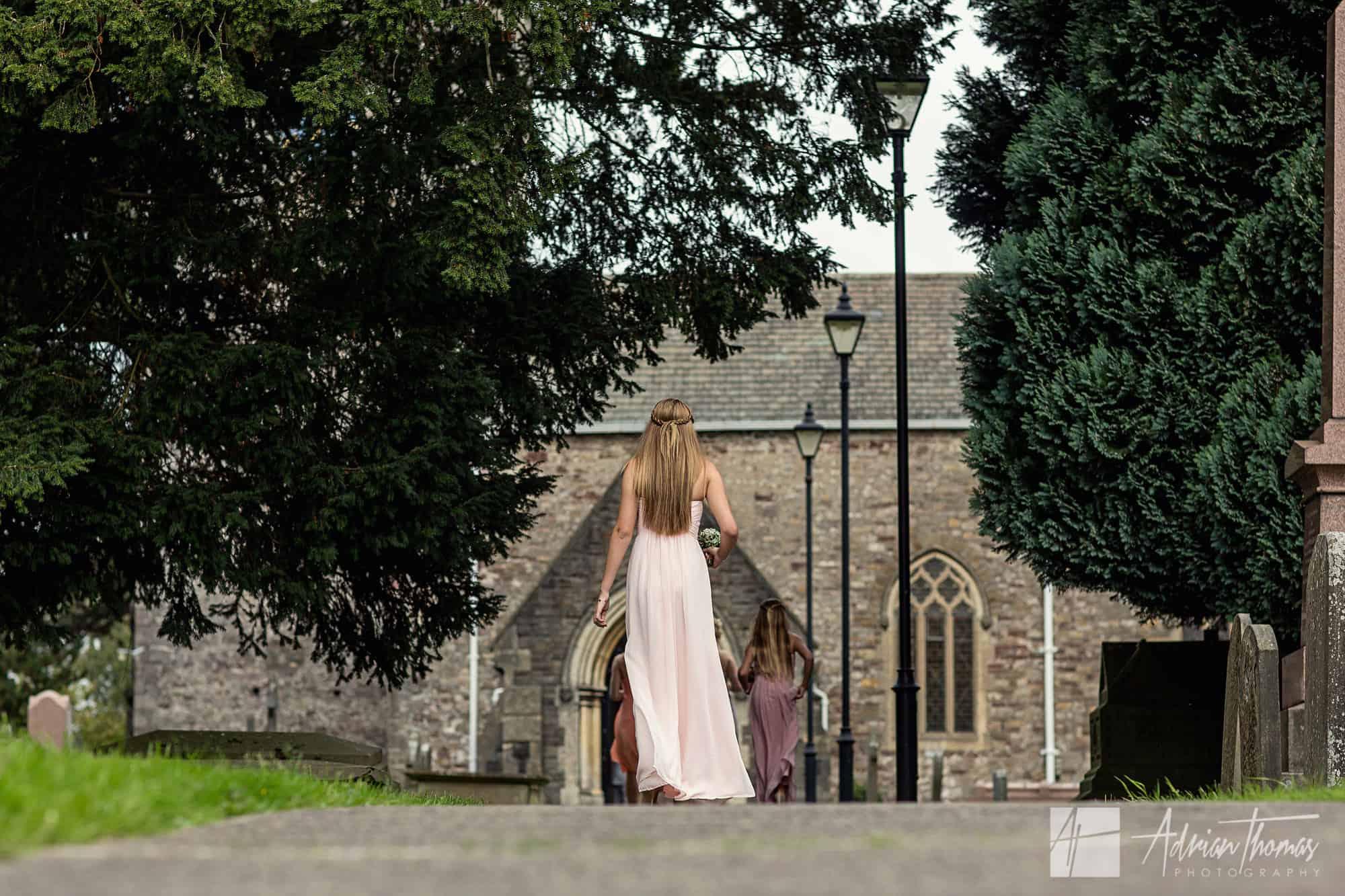 Bridesmaid walking down path at church.