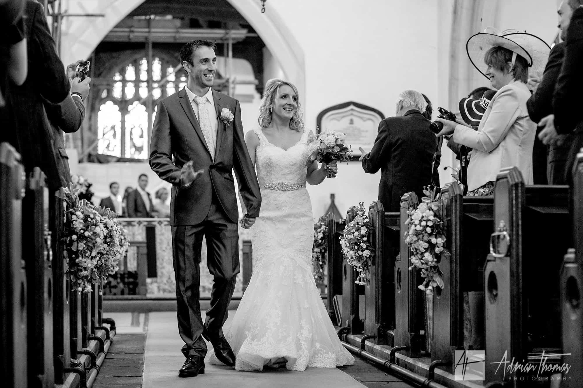 Bride and groom walking down isle after wedding.