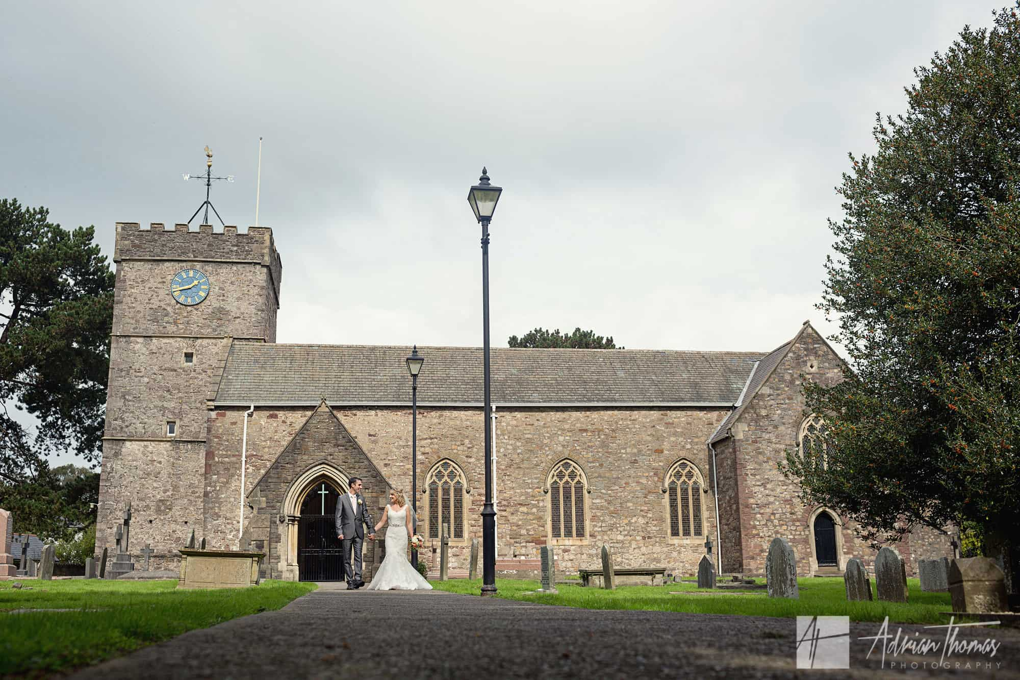 Bride and groom walking at St Basils Church near Cardiff.