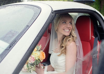 One happy Bride getting into her wedding car.