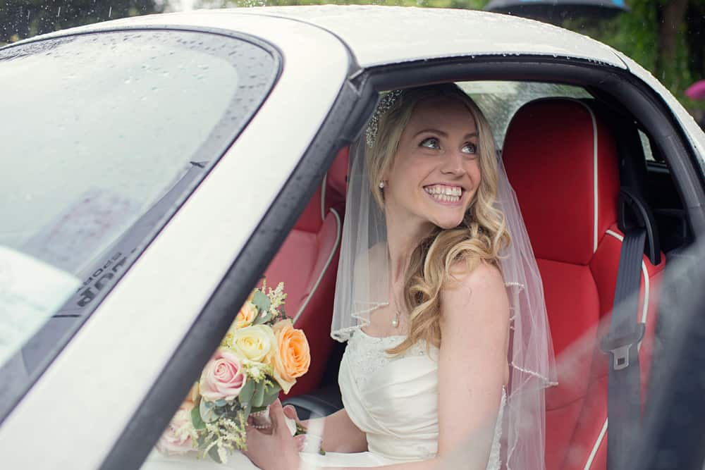 Bride getting into wedding car.