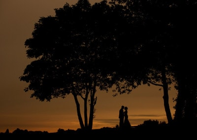 Silhouette of bride and groom at sunset.