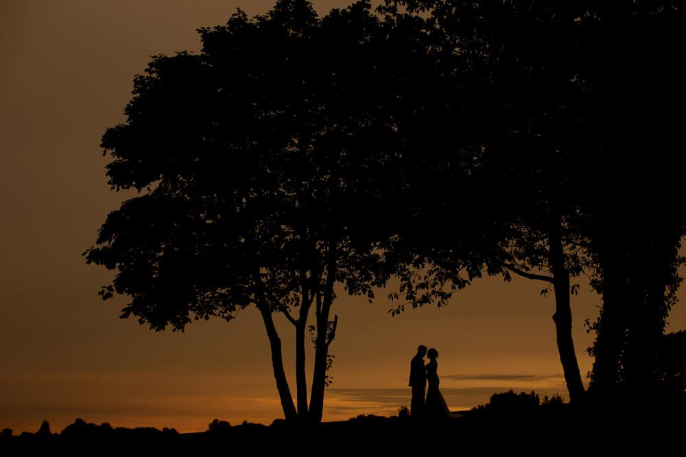 Bride and groom silhouette image at sunset.
