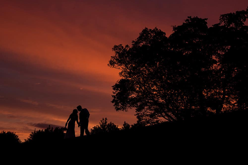 silhouette bride and groom during sun set
