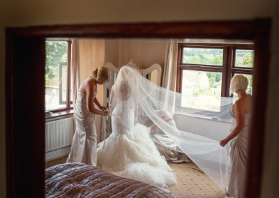 Bride getting ready assisted by bridesmaids.