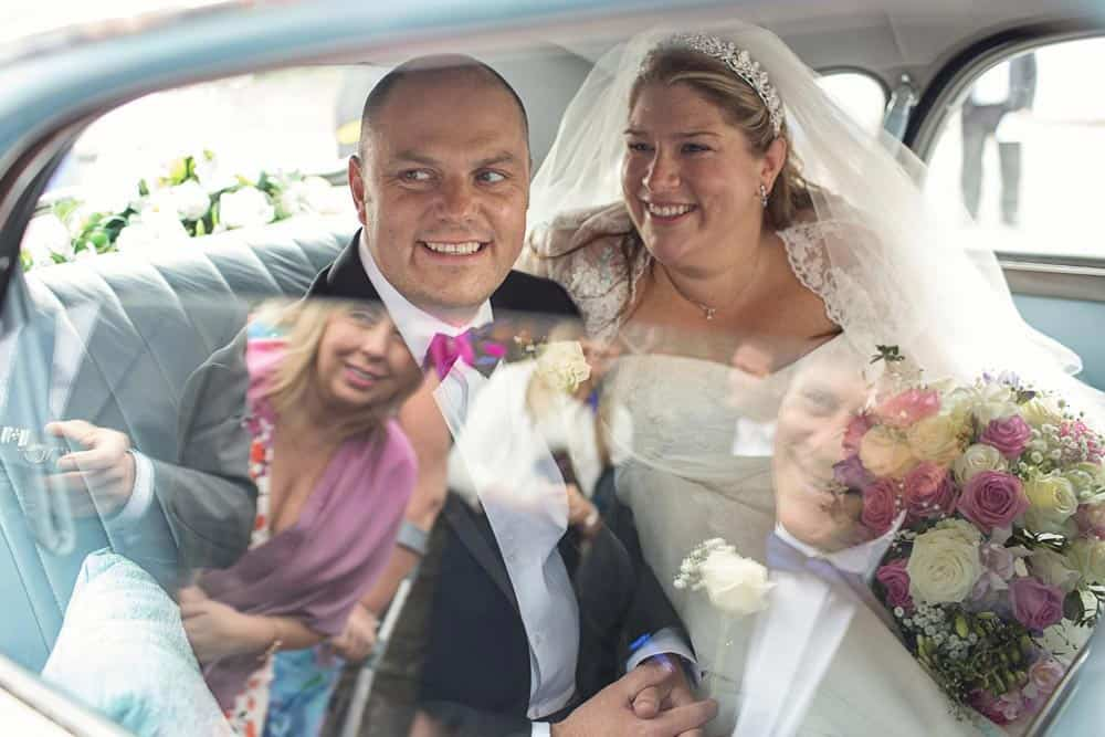 Image of bride and groom in car