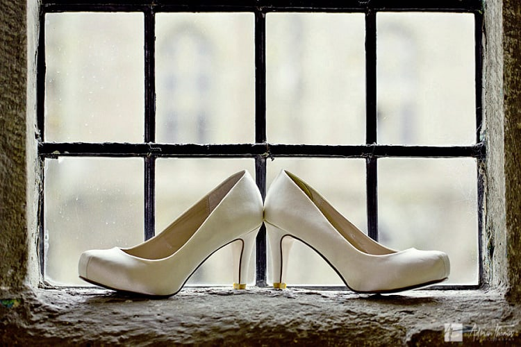 Photo of bridal shoes by window.