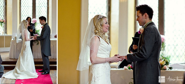 Photograph of bride and groom exchanging rings during wedding at Clearwell Castle.