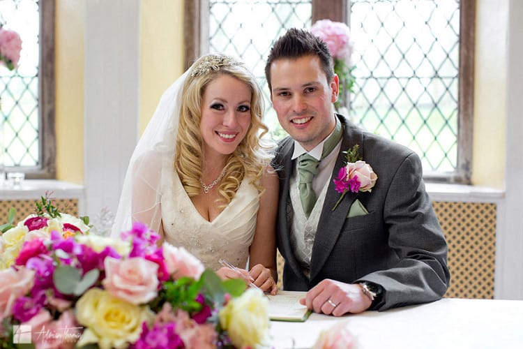 Image of bride and groom signing register during wedding.