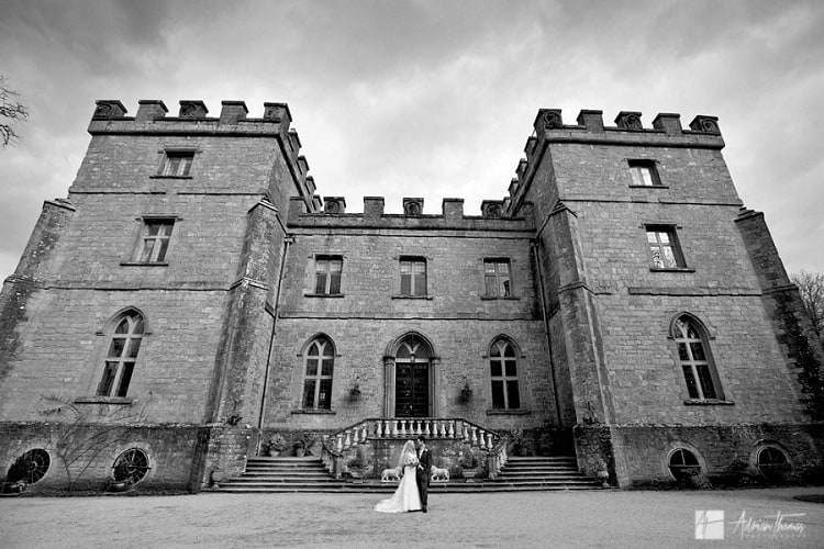 Photo of groom and bride standing outside wedding venue.