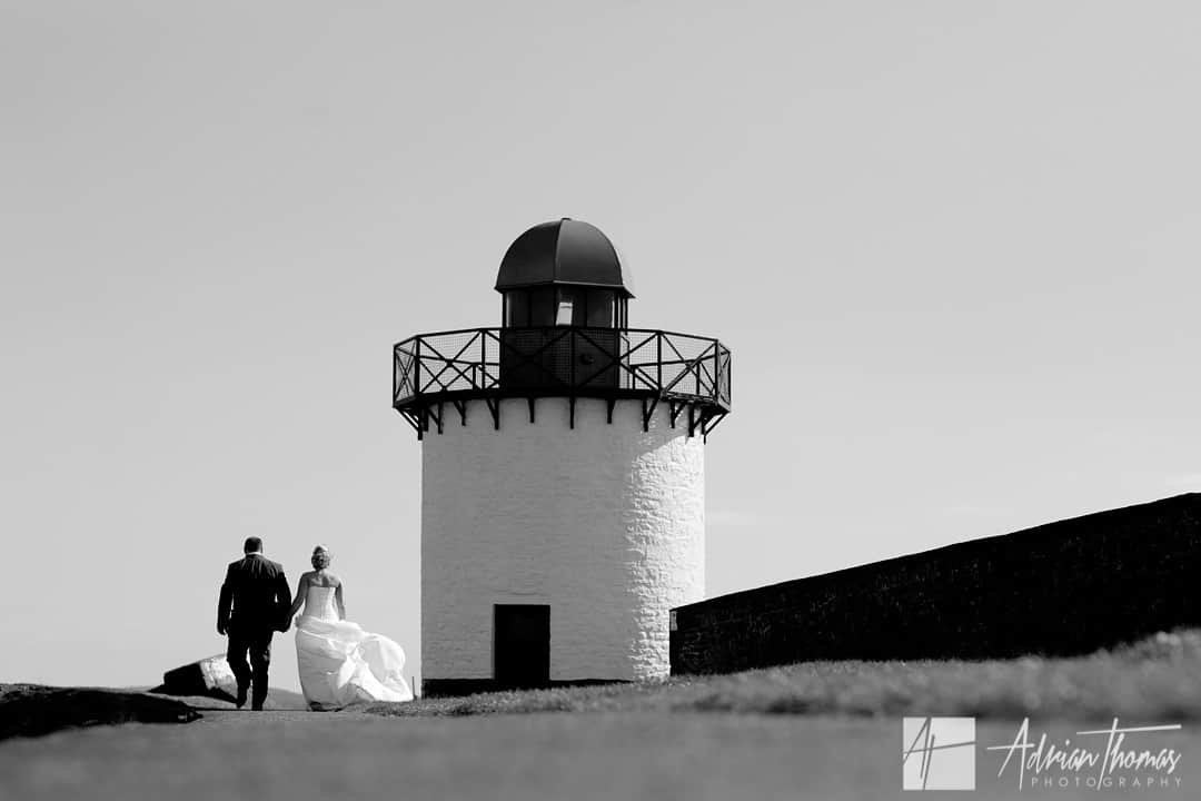 Wedding couple walking by Burry Port Lighthouse during Llanelli wedding.