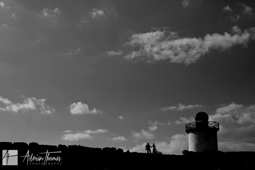 Silhouette of bride and groom walking by Burry Port lighthouse during Llanelli Wedding.