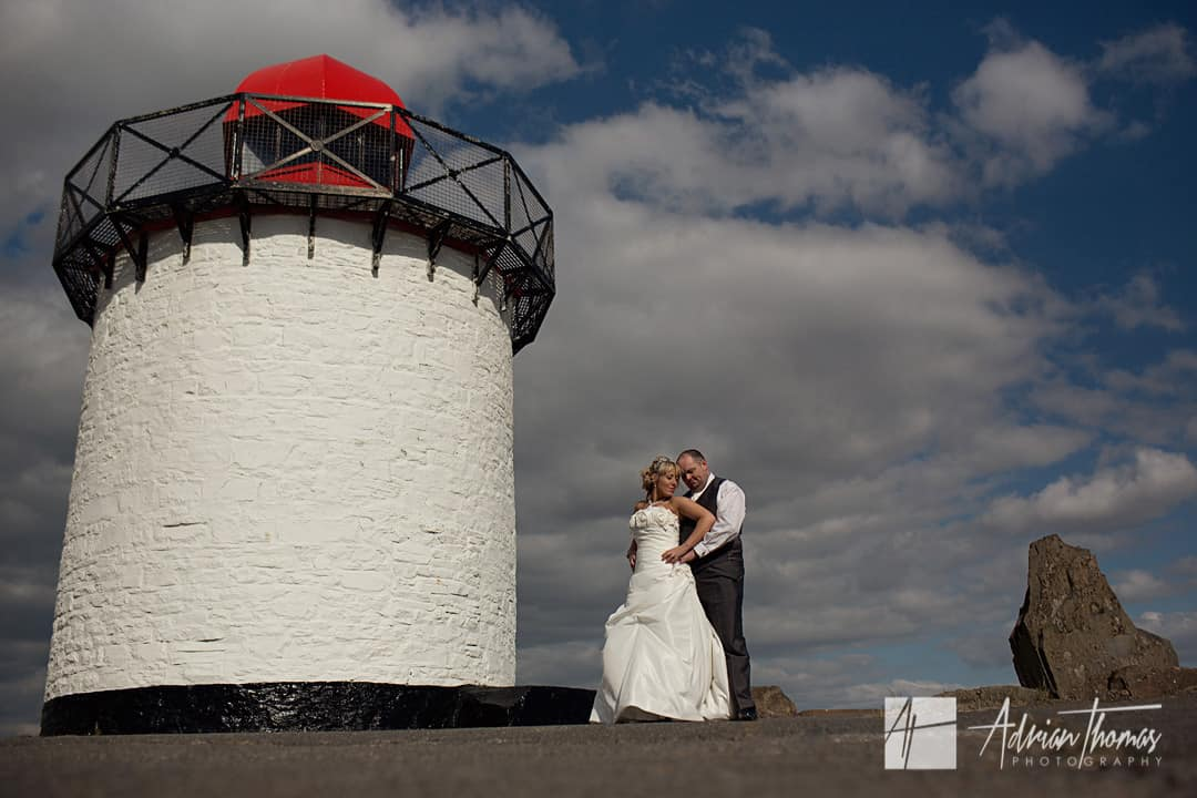 Photo of bride and groom hugging on Burry Port Lighthouse