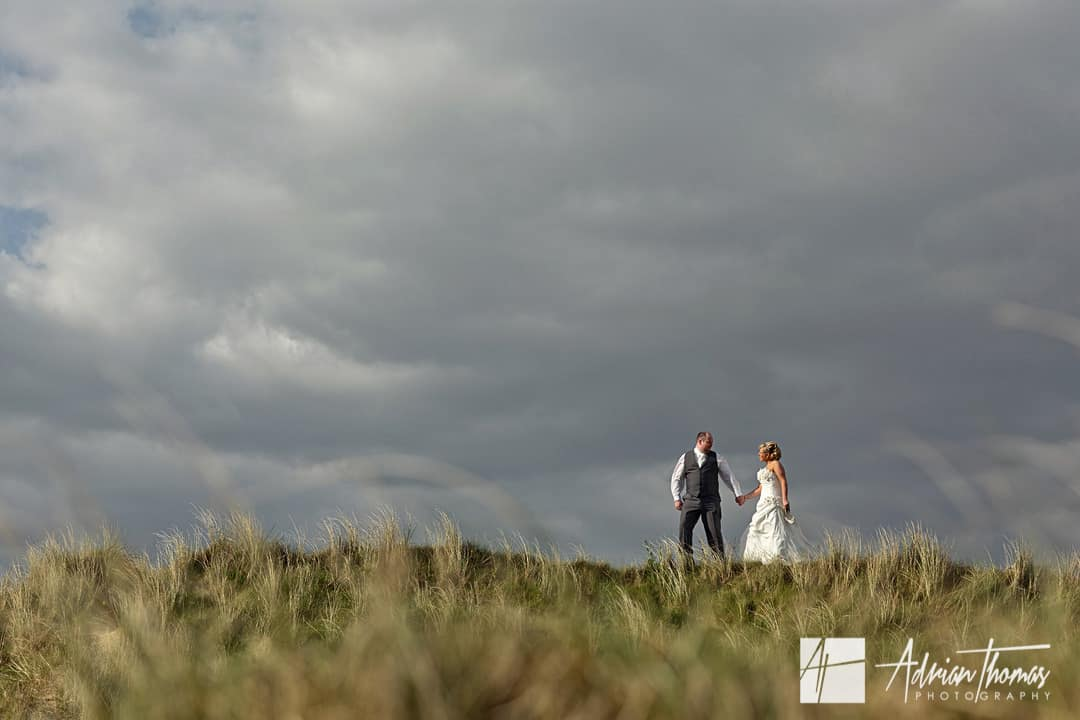 Llanelli wedding with Bride and Groom walking on sand dunes in Burry Port beach
