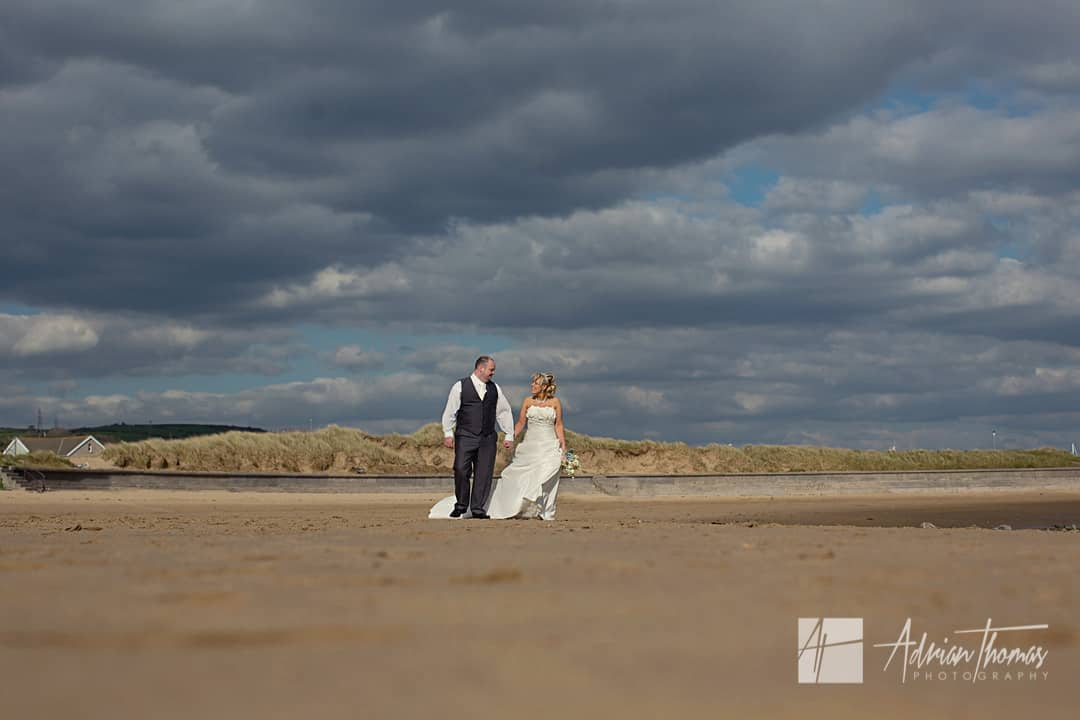 Bride and groom walking on Burry Port beach.