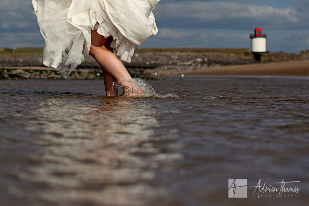 Bride walking through the sea in wedding dress barefooted.